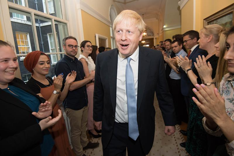 Prime Minister Boris Johnson is clapped into 10 Downing Street by staff after seeing Queen Elizabeth II and accepting her invitation to become Prime Minister and form a new government.