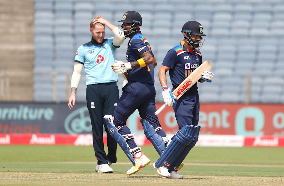 PUNE, INDIA - MARCH 26: India batsman Virat Kohli (r) and Lokesh Rahul pick up runs whilst England bowler Ben Stokes reacts during the 2nd One Day International between India and England at MCA Stadium on March 26, 2021 in Pune, India. (Photo by Surjeet Yadav/Getty Images)