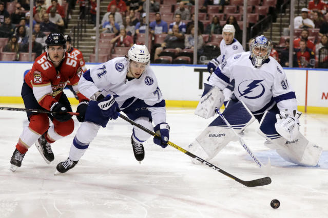 Tampa Bay Lightning's Anthony Cirelli (71) and goalkeeper Andrei Vasilevskiy, right, watch the puck as Florida Panthers' Noel Acciari (55) defends during the second period of an NHL hockey game, Tuesday, Dec. 10, 2019, in Sunrise, Fla. (AP Photo/Luis M. Alvarez)
