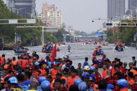 Rescuers use boats to evacuate people from a flooded area in Weihui in central China's Henan Province, Monday, July 26, 2021. Residents laid flowers on Tuesday at the entrance of a subway station where more than a dozen people died after a record-breaking downpour flooded large swaths of Henan province in central China. (Chinatopix via AP)