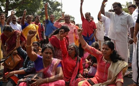 Protestors block traffic and shout slogans reacting to reports of two women of menstruating age entering the Sabarimala temple - Credit: R S Iyer/AP