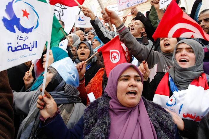 Supporter of the Islamist ruling party Ennahda, hold Tunisian and party flags during a rally in Tunis, Tunisia, Saturday, Feb. 16, 2013. Activists from Tunisia's ruling Islamist party Ennahda denounce in a protest the plans for a government of technocrats to solve the country's crisis. (AP Photo/Amine Landouls)