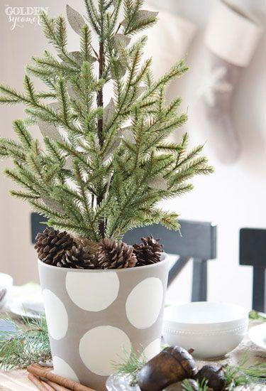 """<p>A miniature evergreen from Michaels, surrounded by faux acorns, cinnamon sticks, and pinecones, stand out on blogger Allison's holiday table. </p><p><strong>Get the tutorial at <a href=""""http://www.thegoldensycamore.com/2013/11/miniature-evergreen-christmas-centerpiece.html"""" rel=""""nofollow noopener"""" target=""""_blank"""" data-ylk=""""slk:The Golden Sycamore"""" class=""""link rapid-noclick-resp"""">The Golden Sycamore</a>.</strong></p>"""