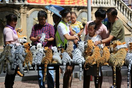 Visitors check on souvenirs displayed at a stall at the Siberia Tiger Park in Harbin, Heilongjiang province China August 5, 2018. Picture taken August 5, 2018. REUTERS/Stringer