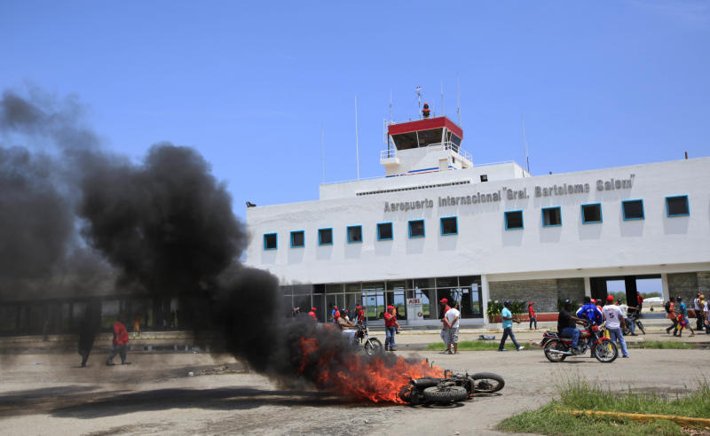A motorcycle burns outside the International airport during clashes in Puerto Cabello, Venezuela, Wednesday, Sept. 12, 2012. Violence broke out before an opposition campaign event got started, between supporters of opposition presidential candidate Henrique Capriles and supporters President Hugo Chavez. Tensions have sporadically erupted into violent clashes and scuffles between supporters of the two candidates ahead of the Oct. 7 presidential vote. (AP Photo/Ariana Cubillos)