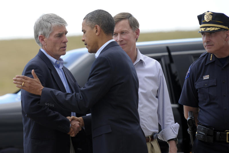 President Barack Obama, second from left, talks with Sen. Mark Udall, D-Colo., left, as Aurora, Colo., Police Chief Daniel Oates, right, and Colorado Gov. John Hickenlooper, second from right, watch, after Obama arrived at at Buckley Air Force Base, Colo., Sunday, July 22, 2012. Obama is traveling to Aurora, Colorado to visit with families of victims of the movie theater shooting as well as local officials. (AP Photo/Susan Walsh)