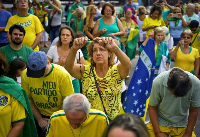 A supporter of Brazilian President Jair Bolsonaro prays during a demonstration to shore up his unltraconservative government as it faces growing opposition