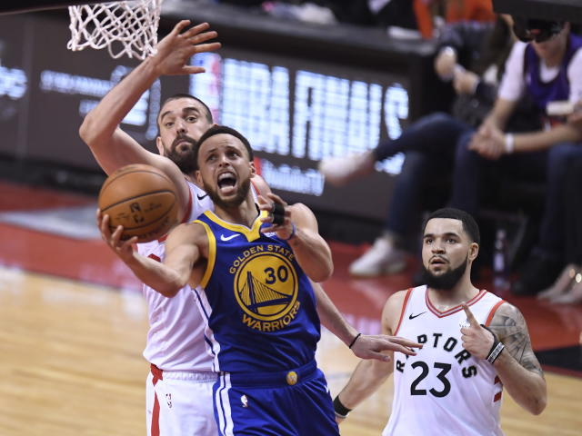 Golden State Warriors guard Stephen Curry (30) goes up for a basket as Toronto Raptors center Marc Gasol and guard Fred VanVleet (23) defend during the first half of Game 1 of basketball's NBA Finals, Thursday, May 30, 2019, in Toronto. (Frank Gunn/The Canadian Press via AP)