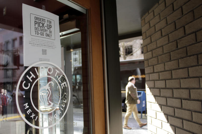 A sign indicating that only carry-out or delivery options are available hangs in the window of a closed Chipotle restaurant in Portland, Ore., Monday, March 16, 2020. Gov. Kate Brown announced a four-week ban on eat-in dining at bars and restaurants throughout the state on Monday to slow the spread of the new coronavirus in Oregon. Restaurants can still offer take-out and delivery. (AP Photo/Gillian Flaccus)