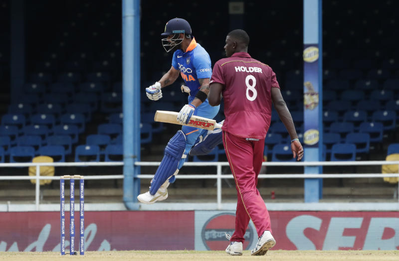 India's captain Virat Kohli jumps into the air while celebrating his century as West Indies bowler captain Jason Holder looks on during their second One-Day International cricket match in Port of Spain, Trinidad, Sunday, Aug. 11, 2019. (AP Photo/Arnulfo Franco)