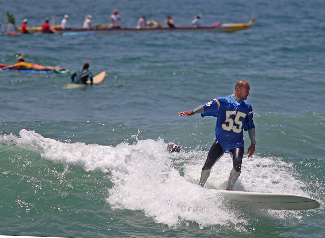 "OCEANSIDE, CA - MAY 6: Surfers ride their boards out into the surf for a ceremony during a ""paddle-out"" in honor of NFL star Junior Seau on May 6, 2012 in Oceanside, California.  Seau, who played for various NFL teams including the San Diego Chargers, Miami Dolphins and New England Patriots was found dead in his home on May 2nd of an apparent suicide.  Family members have decided to donate his brain for research on links between concussions and possible depression. (Photo by Sandy Huffaker/Getty Images)"