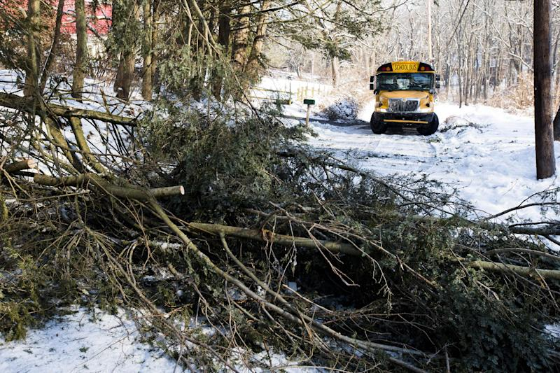 A school bus is block by down trees in the aftermath of a winter storm, Friday, Feb. 7, 2014, in Downingtown, Pa. Schools canceling classes because of winter weather in at least 10 states have used up the wiggle room in their academic calendars, forcing them to schedule makeup days or otherwise compensate for the lost time. (AP Photo/Matt Rourke)
