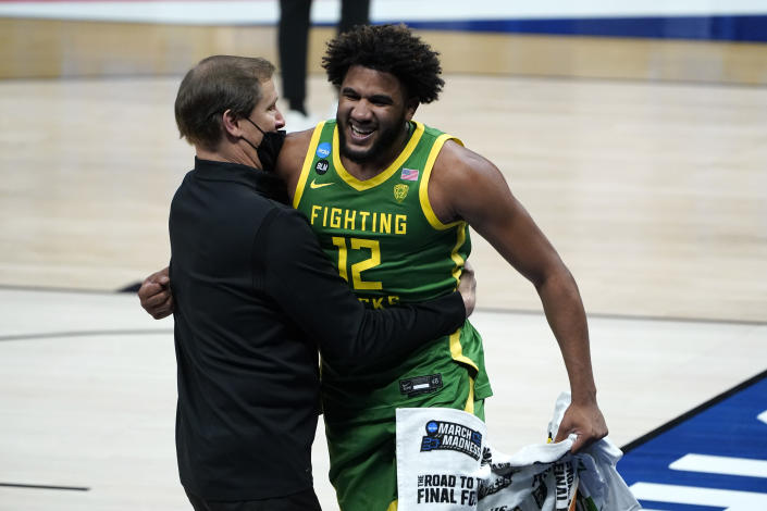 Oregon head coach Dana Altman and LJ Figueroa (12) celebrate after beating Iowa 95-80 in a men's college basketball game in the second round of the NCAA tournament at Bankers Life Fieldhouse in Indianapolis, Monday, March 22, 2021. (AP Photo/Paul Sancya)