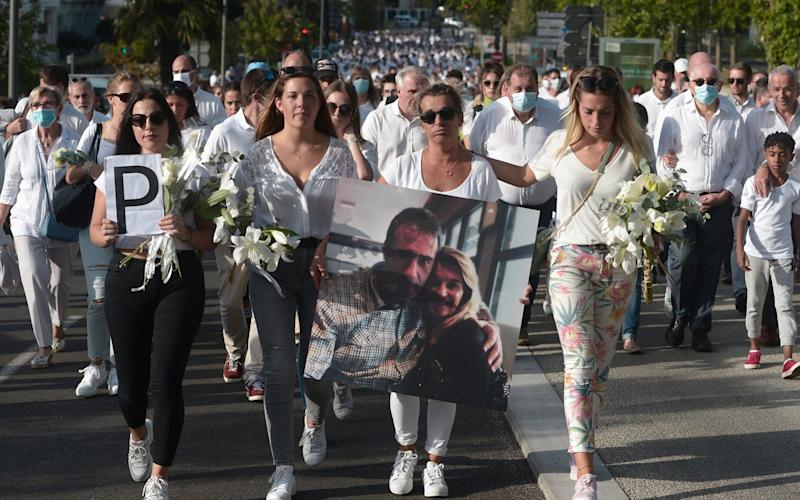 Veronique Monguillot (centre), wife of bus driver Philippe Monguillot, holds a picture of her husband during a white march in Bayonne, France - IROZ GAIZKA/AFP