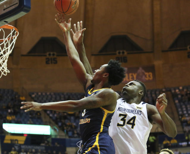 Northern Colorado's Tre'Shon Smoots, left, shots the ball as he's defended by West Virginia's Oscar Tshiebwe, right, during the first half of an NCAA college basketball game Monday Nov. 18, 2019, Morgantown, W.Va. (AP Photo/Kathleen Batten)