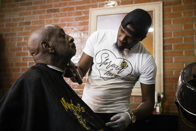 Brennon Jones, right, trims Larry Hemphill's beard for free as part of his makeover Mondays in Philadelphia Nov. 20. Jones, who originally provided free haircuts to homeless people on the street, now continues to donate his services to anyone who is in need at a shop that was given to him by Sean Johnson. (Photo: Matt Rourke/AP)
