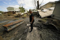 Audrey Trufant Salvant stands near a casket that floated in floodwaters from a nearby cemetery to her home in Ironton, La., Monday, Sept. 27, 2021. A month after Hurricane Ida roared ashore with 150-mph (241-kph) winds, communities all along the state's southeastern coast — Ironton, Grand Isle, Houma, Lafitte and Barataria — are still suffering from the devastating effects of the Category 4 storm. (AP Photo/Gerald Herbert)