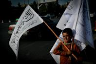 A boy carries Taliban flags to sell in the Karte Mamorin neighbourhood of Kabul on Sunday