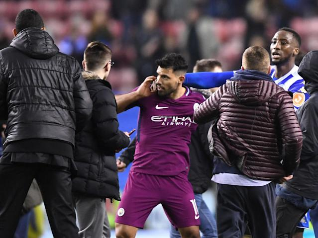 Wigan win over Manchester City marred by violent pitch invasion as Sergio Aguero clashes with fan