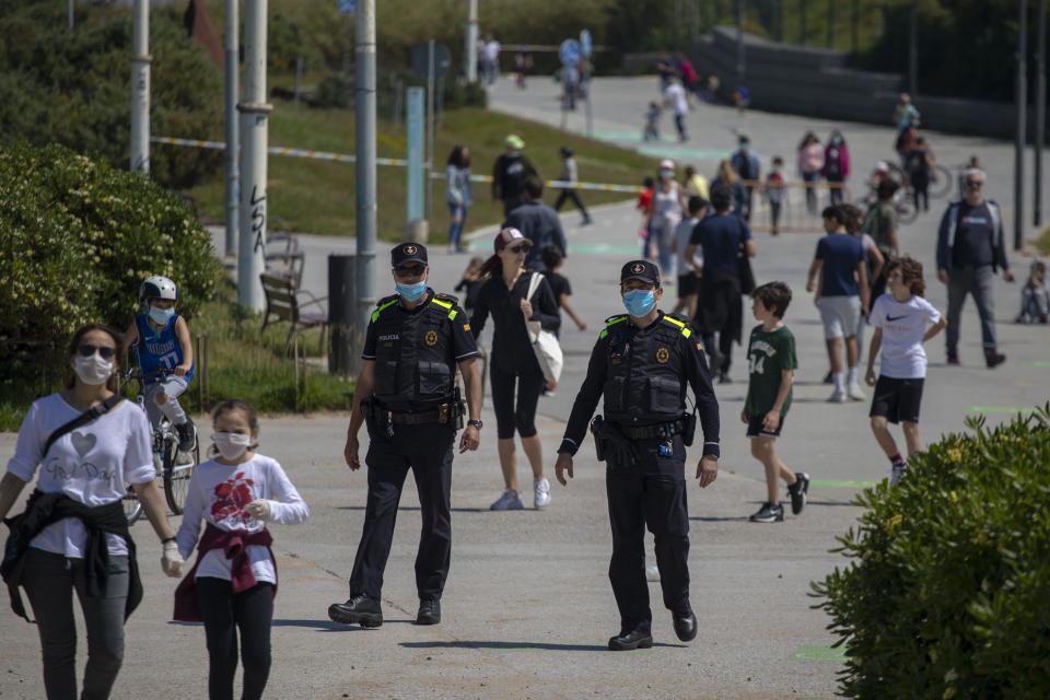 Catalan police officers patrol as families with their children walk along a boulevard in Barcelona, Spain, Sunday, April 26, 2020 as the lockdown to combat the spread of coronavirus continues. On Sunday, children under 14 years old will be allowed to take walks with a parent for up to one hour and within one kilometer from home, ending six weeks of compete seclusion. (AP Photo/Emilio Morenatti)