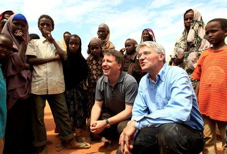 FILE PHOTO: Britain's Secretary of State for International Development Andrew Mitchell (2nd R) and NGO Save the Children Chief Executive Justin Forsyth (C) talk with newly-arrived refugees at the Dagahaley refugee camp in Dadaab, near Kenya's border with Somalia, July 16, 2011. Mitchell visited Dadaab refugee camps, where he met displaced families forced to leave their homes in Somalia in order to survive. REUTERS/Thomas Mukoya/File Photo