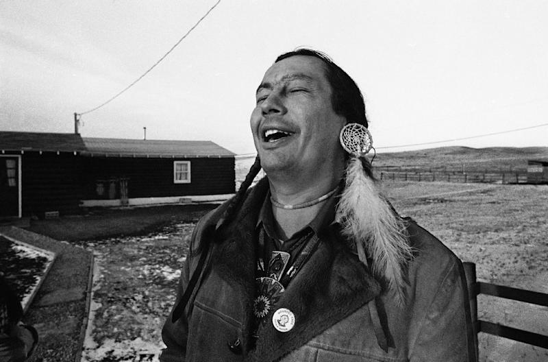 "FILE - In a Feb. 4, 1974 file photo, American Indian Movement (AIM) leader Russell Means, who is challenging incumbent Oglala Sioux Tribal President Richard Wilson in Thursday's election on the Pine Ridge Indian Reservation, laughs at news report which quoted Wilson as saying he will give AIM 10 days to get off the reservation after he is reelected ""or else"", in Pine Ridge, S.D. Means, a former American Indian Movement activist who helped lead the 1973 uprising at Wounded Knee, reveled in stirring up attention and appeared in several Hollywood films, died early Monday, Oct. 22, 2012 at his ranch in in Porcupine, S.D., Oglala Sioux Tribe spokeswoman Donna Solomon said. He was 72. (AP Photo/Jim Mone, File)"