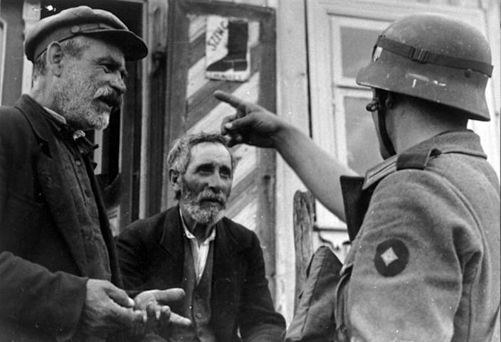 Image: Lithuanian Jews and a German Wehrmacht Soldier during the Holocaust (Universal History Archive / via Getty Images)