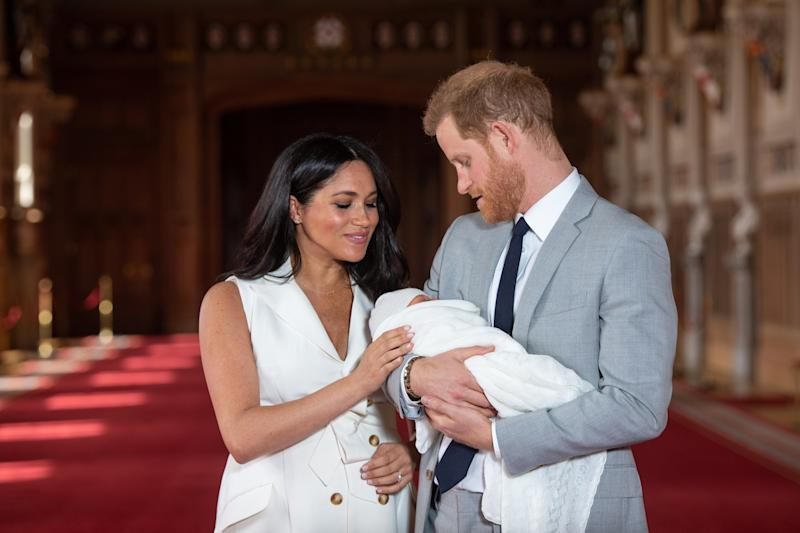 Prince Harry, Duke of Sussex and Meghan, Duchess of Sussex, pose with their newborn son Archie Mountbatten Windsor during a photocall in St George's Hall at Windsor Castle