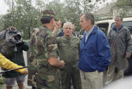 FILE - In this Aug. 26, 1992, file photo, U.S. President George H. Bush confers with Louisiana Governor Edwin Edwards, center, and a Louisiana National Guardsman in New Iberia, amid damage caused by Hurricane Andrew. Edwin Washington Edwards, the high-living four-term governor whose three-decade dominance of Louisiana politics was all but overshadowed by scandal and an eight-year federal prison stretch, died Monday, July 12, 2021 . He was 93. Edwards died of respiratory problems with family and friends by his bedside, family spokesman Leo Honeycutt said. He had suffered bouts of ill health in recent years and entered hospice care this month at his home in Gonzales, near the Louisiana capital. (AP Photo/Greg Gibson, File)
