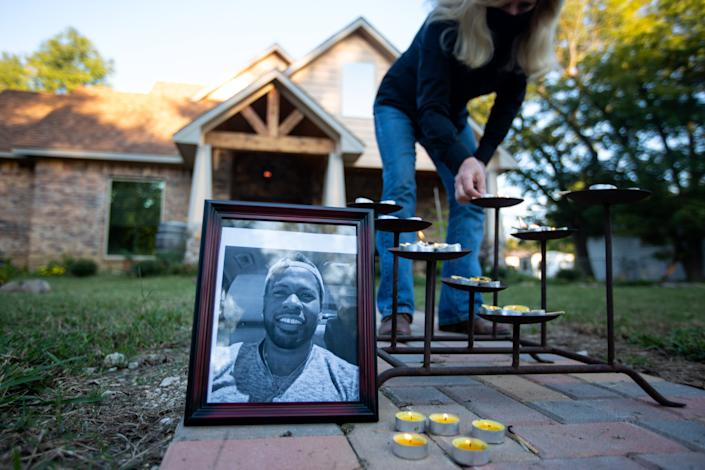 Picture of Jonathan Price with candles in front of a residence in Wolfe City, Texas. (Photo by Montinique Monroe/Getty Images)