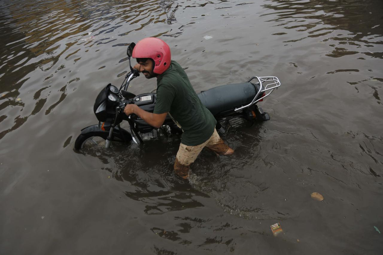 AHMEDABAD, INDIA - AUGUST 10: A man carries his motorbike on a waterlogged road after heavy rain, on August 10, 2019 in Ahmedabad, India. Heavy rains continued in many places in Gujarat on Friday, with the India Meteorological Department (IMD) issuing a warning of heavy to very heavy rainfall over the next two days. According to official sources, 11 people died in rain related incidents in rain-hit Gujarat. Heavy rains battered the State, disrupting normal life. (Photo by Siddharaj Solanki/Hindustan Times via Getty Images)