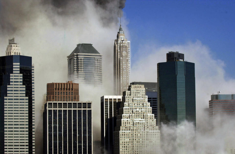Smoke billows through buildings in Manhattan as seen from Brooklyn after the collapse of New York's World Trade Center, Tuesday, Sept. 11, 2001. (AP Photo/Kathy Willens)