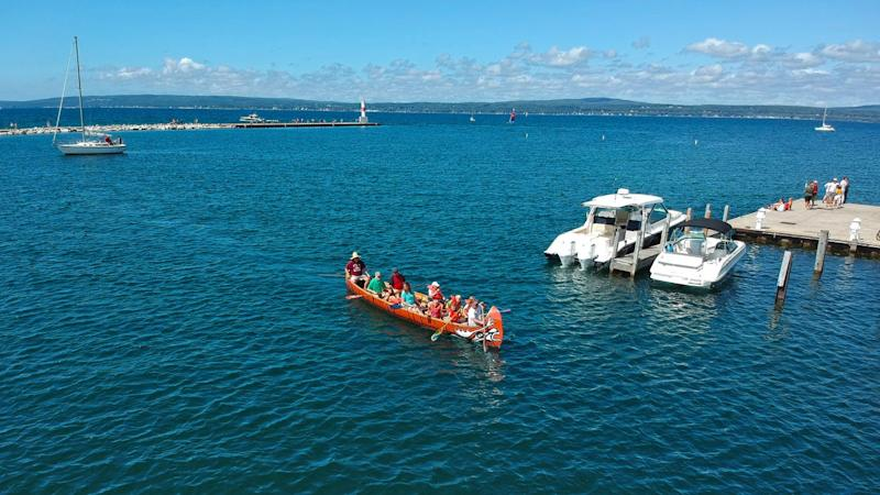 A group canoes aboard the Jiimaan, a 32-foot community canoe built by members of the Little Traverse Bay Bands of Odawa Indians. The canoe was utilized for remote-operated underwater vehicle examinations of the area of the Straits of Mackinac near the Line 5 oil pipeline.