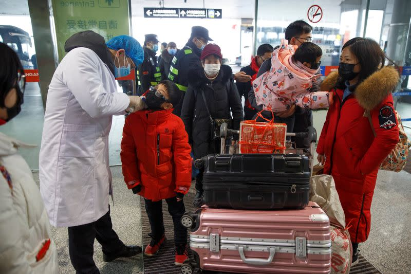 A medical official takes the body temperature of a child at the departure hall of the airport in Changsha
