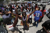Supporters of former Haitian President Jean-Bertrand Aristide gather near the airport for his expected arrival from Cuba, where he underwent medical treatment, in Port-au-Prince, Haiti, Friday, July 16, 2021. Aristide's return adds a potentially volatile element to an already tense situation in a country facing a power vacuum following the July 7 assassination of President Jovenel Moïse. (AP Photo/Fernando Llano)