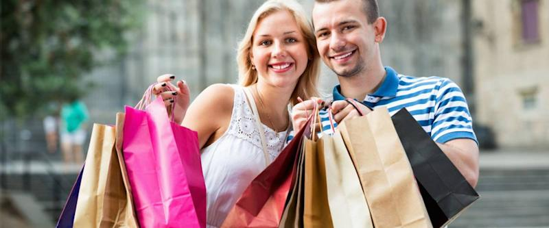 Young man and beautiful woman holding shopping paper bags and looking happy in town