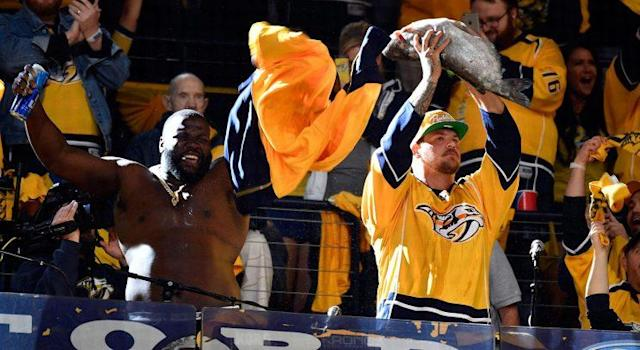 A member of the Tennessee Titans holds up a catfish to pump up the Nashville Predators crowd before Game 3 of the Western Conference final. (Christopher Hanewinckel-USA TODAY Sports)