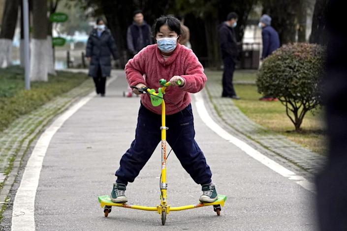 A child wearing a mask rides on a skate scooter in Wuhan.