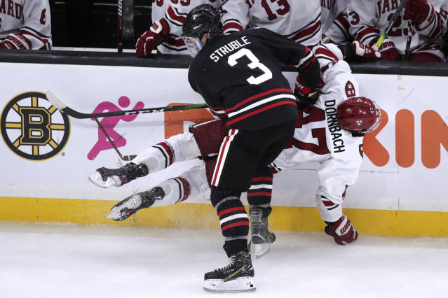 Harvard forward Casey Dornbach (47) is checked against the boards by Northeastern defenseman Jayden Struble (3) during the second period of the NCAA hockey Beanpot Tournament in Boston, Monday, Feb. 3, 2020. (AP Photo/Charles Krupa)