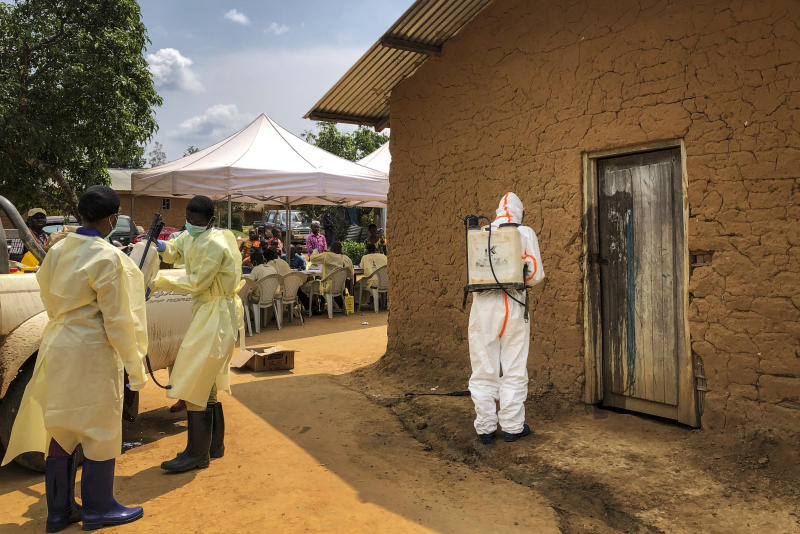 A worker from the World Health Organization (WHO) decontaminates the doorway of a house on a plot where two cases of Ebola were found, in the village of Mabalako, in eastern Congo Monday, June 17, 2019. Health officials in eastern Congo have begun offering vaccinations to all residents in the hotspot of Mabalako whereas previous efforts had only targeted known contacts or those considered to be at high risk. (AP Photo/Al-hadji Kudra Maliro)