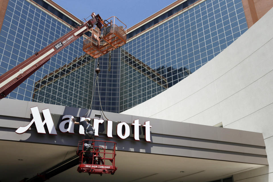 FILE - In this Tuesday, April 30, 2013, file photo, a man works on a new Marriott sign in front of the former Peabody Hotel in Little Rock, Ark. Marriott says its business is steadily improving, Monday, Aug. 10, 2020, with 91% of its hotels now reopen and business travel reemerging in China. (AP Photo/Danny Johnston, File)