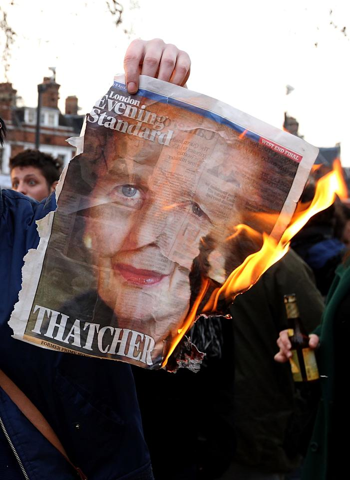 UNSPECIFIED, UNITED KINGDOM - APRIL 08:  A lady burns the front page of a newspaper displaying an image of former British Prime Minister Margaret Thatcher as she and others celebrate her death in Brixton on April 8, 2013 in London, England. Lady Thatcher has died this morning following a stroke aged 87. Margaret Thatcher was the first female British Prime Minster and governed the UK from 1979  to 1990. She led the UK through some turbulent years and contentious issues including the Falklands War, the miners' strike and the Poll Tax riots.   (Photo by Danny E. Martindale/Getty Images)