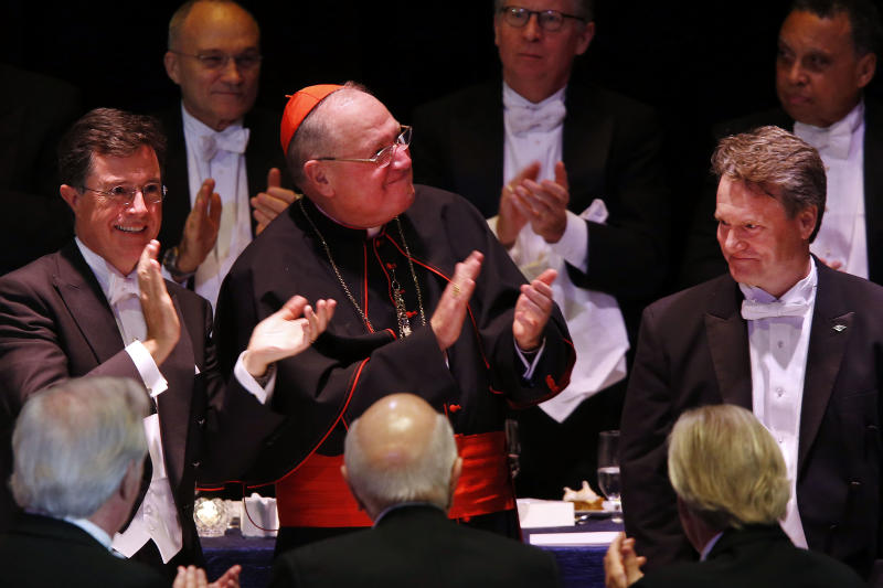 Keynote speaker Stephen Colbert, left, and Cardinal Timothy Dolan, center, applaud Brian Moynihan, President and CEO of Bank of America, during the Alfred E. Smith Memorial Foundation dinner, a charity gala organized by the Archdiocese of New York, at the Waldorf-Astoria hotel, Thursday, Oct. 17, 2013, in New York. (AP Photo/Jason DeCrow)