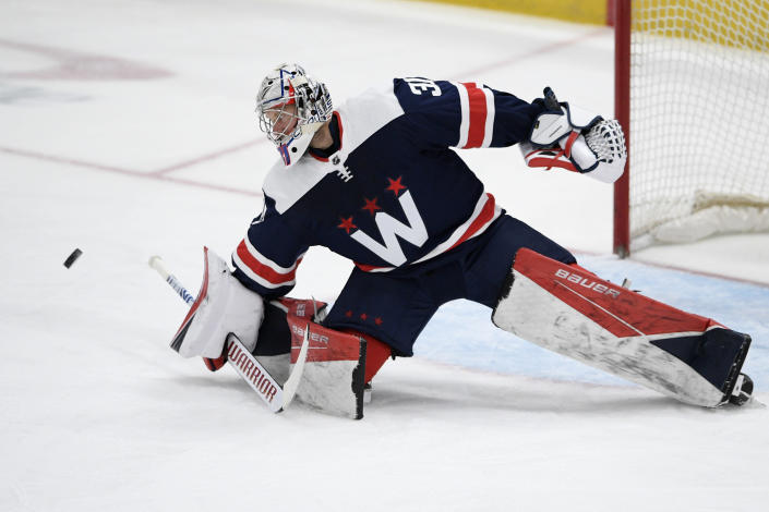 Washington Capitals goaltender Craig Anderson (31) leans towards the puck during the first period of an NHL hockey game against the New Jersey Devils, Sunday, Feb. 21, 2021, in Washington. (AP Photo/Nick Wass)