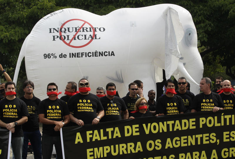 """Federal police protest for better labor conditions outside the venue where Brazil's coach is announcing his squad for the upcoming World Cup where they placed a white elephant doll symbolizing public waste that reads in Portuguese """"No police investigation. 96% inefficiency"""" in Rio de Janeiro, Brazil, Wednesday, May 7, 2014. Federal police are threatening to go on strike during the international soccer tournament if their demands are not met. (AP Photo/Silvia Izquierdo)"""