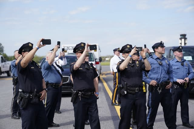 Scores of Trump supporters lined the route of his motorcade, while even local police took photos of the president (Evan Vucci/AP)