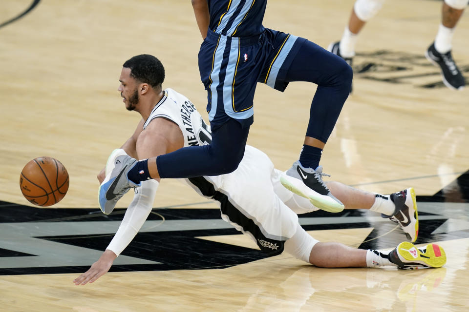 San Antonio Spurs guard Quinndary Weatherspoon (15) dives past Memphis Grizzlies guard Desmond Bane (22) for a loose ball during the second half of an NBA basketball game in San Antonio, Monday, Feb. 1, 2021. (AP Photo/Eric Gay)