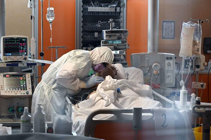 A medical worker in protective gear tends to a COVID-19 patient in the intensive care unit of a hospital near Rome.