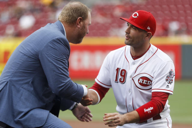 Cincinnati Reds first baseman Joey Votto (19) shakes hands with Cincinnati Reds Hall of Fame inductee and former player Adam Dunn, left, during an induction ceremony before the team's baseball game against the Pittsburgh Pirates, Saturday, July 21, 2018, in Cincinnati. (AP Photo/John Minchillo)