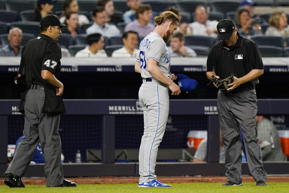 Kansas City Royals relief pitcher Josh Staumont (63) presents his cap and glove to second base umpire Bill Miller after the sixth inning of a baseball game against the New York Yankees, Wednesday, June 23, 2021, at Yankee Stadium in New York. Home plate umpire Gabe Morales (47) watches, left. (AP Photo/Kathy Willens)